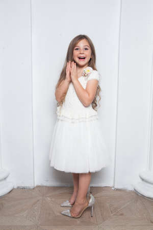 Little princess - excited emotional cute girl in fashion white dress having fun and wearing big mothers sparkle high heels shoes on white background. Free space for text mockup 免版税图像