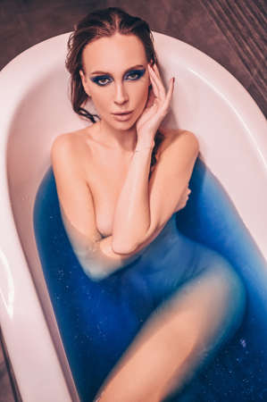 Beautiful young woman with fashion make up, posing bathing in a retro tub full of colored blue cosmic bath bomb water. Spa and beauty salon concept, body and skin care