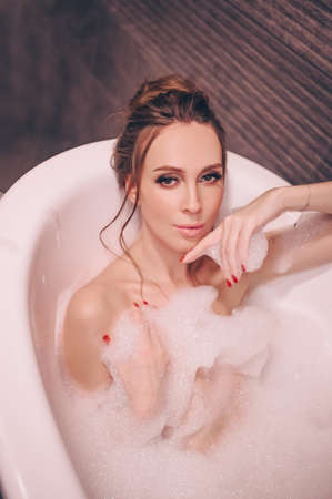Beautiful young woman with make up and hairstyle relaxes bathing in a retro tub full of bubble foam. Spa and beauty salon concept, body and skin care Reklamní fotografie