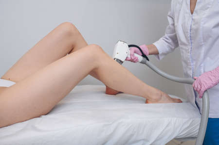 Laser epilation and cosmetology in beauty salon. Hair removal procedure. Laser epilation, cosmetology, spa, and hair removal concept. Beautiful blonde woman getting hair removing on legs Stock fotó