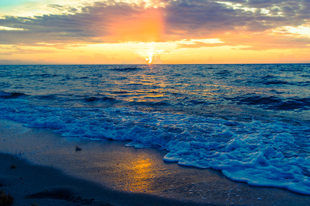 sun reflection of the blue ocean waves with colorful sunrise background