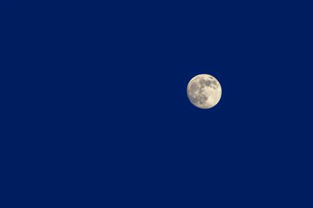 waxing gibbous moon in blue sky