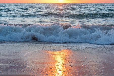 olas rompiendo en la playa y reflejando el amanecer Foto de archivo