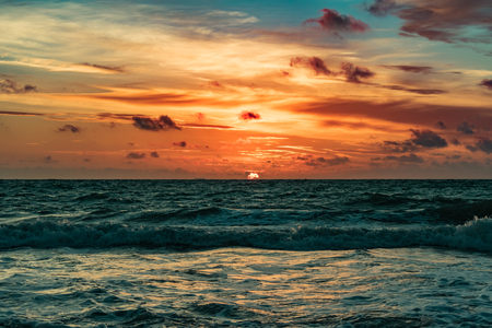 orange sun rising on the horizon on a windy morning with wavy green waters Stock Photo