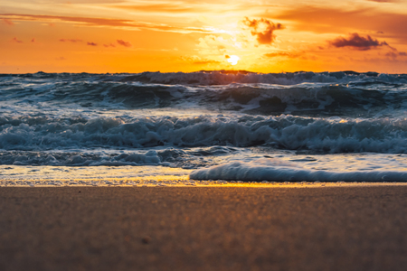 Close up of wet sand as blue waves crash on the shore and the sun rises on the horizon with an orange glow