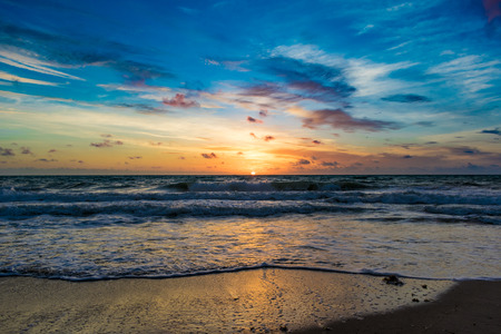 Blue sky above the sun rising on the horizon and reflecting off the water on a windy morning at the beach Stock Photo