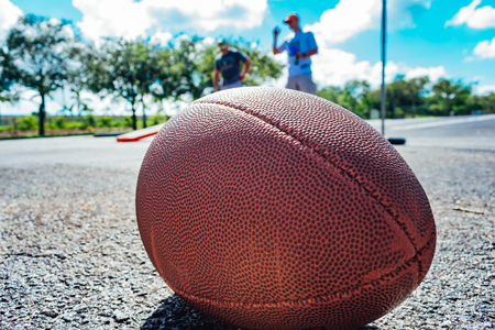 close up of an american football on the ground with people playing cornhole in the background while tailgating before the game Stock Photo