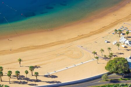 Top view of natural clear deep blue Atlantic ocean and gold sand beach with umbrellas and palms.