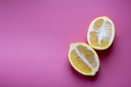 Flat lay composition with yellow lemons and space for text on color pink background Reklamní fotografie