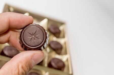 Hand of a man holding a chocolate from a box of chocolates.