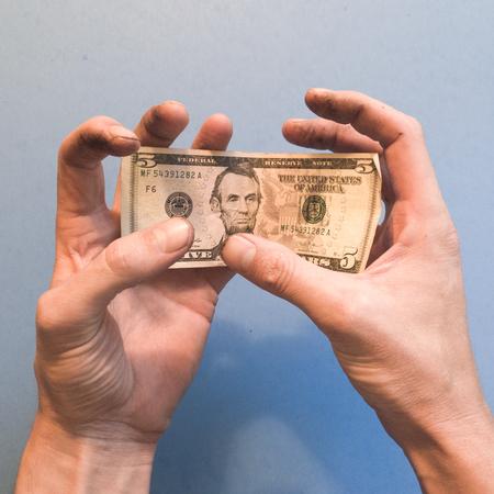 Hand awkwardly holding $5 Reklamní fotografie