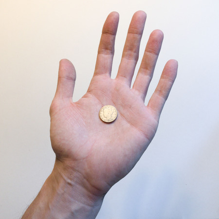 Hand holding a liberty nickle Imagens