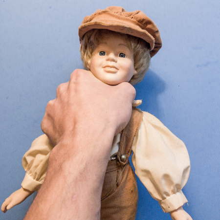 Hand choking a doll