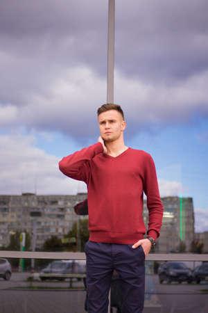 chico en una chaqueta roja está de pie sobre un fondo espejo