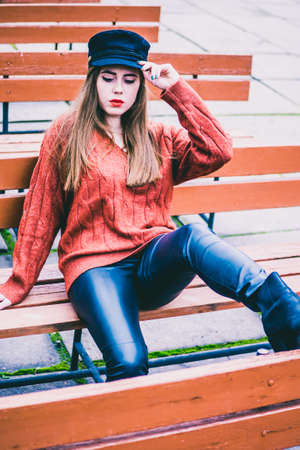 fashionable girl in a cap on a park bench