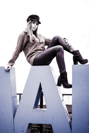 fashionable girl is sitting on the letters