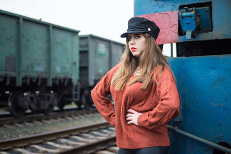 a fashionable girl in a cap standing on the background of a diesel locomotive and a passing freight train