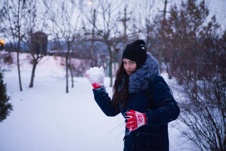 the girl is holding a snow in her hands