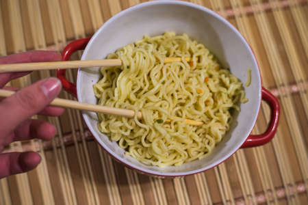noodles in a soup tureen with bamboo sticks