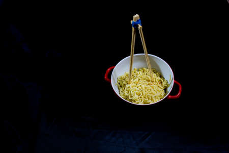 noodles and bamboo sticks on a black background