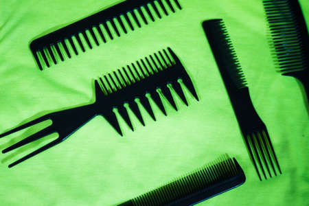 Hairbrushes for styling and hair cuts on a green background.