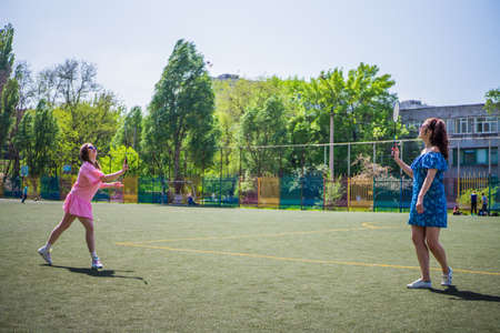 Girls girlfriends playing the game of badminton on the football field on a sunny summer day Stock Photo