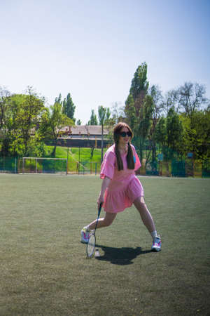 Girl playing a game of badminton on a football field on a sunny summer day