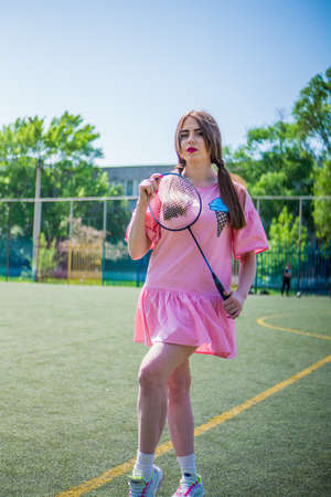 A girl on a football field on a sunny and bright day goes in for sports and plays a game of badminton