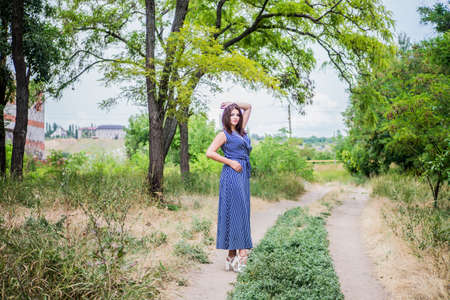 Girl brunette in a blue long dress on a dirt road against a background of trees and nature