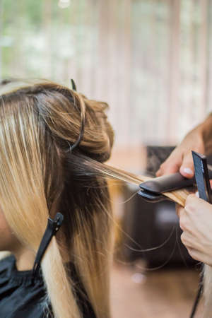 The hairdresser pulls the client hair, after washing his head, applying nutrients to the hair and drying the hair with a hair dryer, botox hair, restoring and nourishing the hair