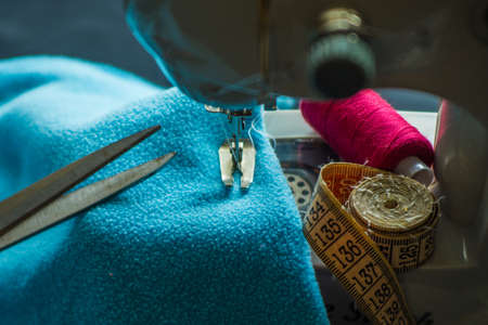 Sewing machine at work, scissors and threads