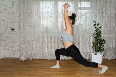 An overweight girl is involved in sports, losing weight, doing yoga exercises at home. Фото со стока