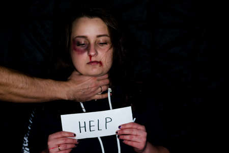 A battered young wife with a bruised lip and nose, suffers from violence, beatings and bullying of her husband. A husband holds his battered and frightened wife by the throat.