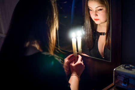 A girl in a dark room, divines with candles in her hand in front of a mirror, looks in her reflection and sees her future.