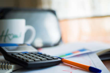 On the home table are stock and finance charts with a calculator, a coffee mug, a pencil, a marker pen, two notebooks, a smartphone and a tablet for remote work. Work at home.