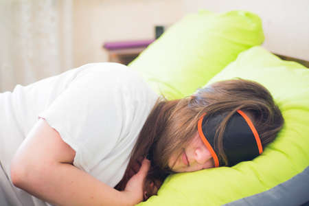 A young girl with a blindfold for sleeping sleeps in her bed on a brightly green-colored pillow and does not want to wake up to work. Stock Photo