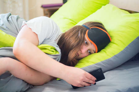A young and sad girl woke up early in the morning and lies in bed on a pillow under a blanket and looks at the clock in her smartphone and does not want to get up from a warm bed.