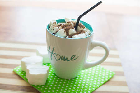 Coffee with white marshmallows, grated chocolate, a black straw in a mug with the inscription house, on a green napkin, on a wooden table.