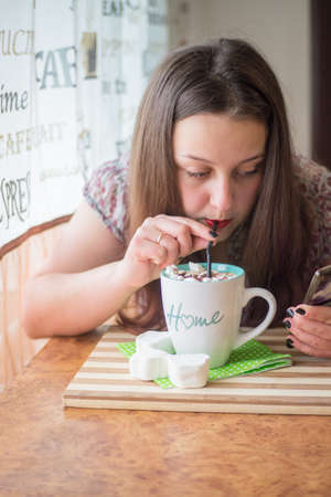 A young and beautiful girl sits in a cafe drinking delicious coffee with marshmallows sprinkled with chocolate chips through a black straw and reading the news from a smartphone. Stockfoto