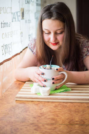 A young girl is waiting for a meeting in a cafe with a cup of coffee, with white marshmallow sprinkled with chocolate chips and a black straw on a wooden table.