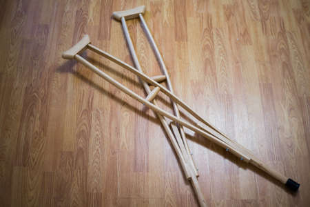 Wooden crutches on a wooden floor, for the movement of people with disabilities, people with fractures and sprains, or bone defects.