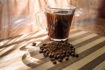 Brewed black coffee stands in a transparent cup on a wooden plank with whole, roasted beans and instant coffee scattered on it.