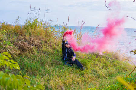 A boy in a black sports suit sits on the green grass, the boy has a crimson smoke bomb in his hand and it smokes into the sky.
