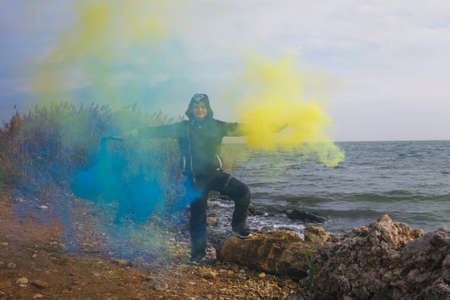 A boy twists blue and yellow smoke bombs in both hands on the seashore with a beautiful view of the horizon.