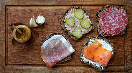 Four sandwiches on a wooden cutting board photo