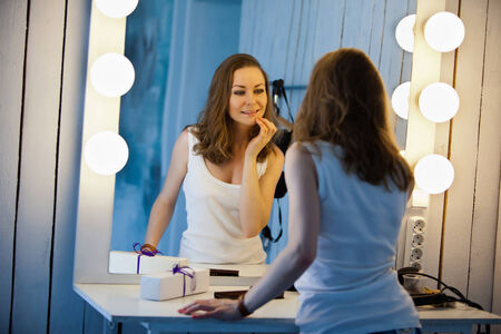 mirror frame: Beautiful young woman in white shirt looking at her reflection in a dressing room mirror