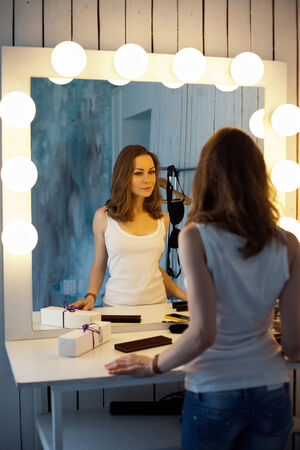 femme fatale: Beautiful young woman in white shirt looking at her reflection in a dressing room mirror
