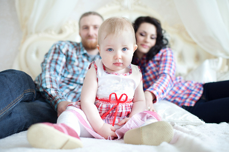 blue eyes: Mother, father and their daughter sitting on the bed