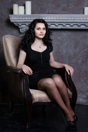 Beautiful woman with dark hair sitting in vintage chair