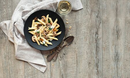 Pasta with mushrooms on rustic wooden table with a space for your text